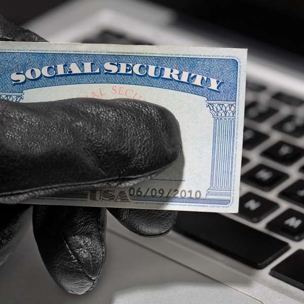A thief holding a social security card is seen in this undated, staged image. (Credit: Getty Images)