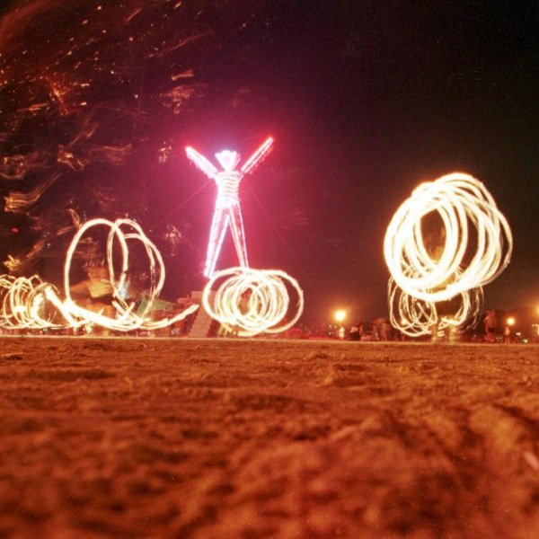 """Dancers at the """"Burning Man"""" festival create patterns with fireworks in the Black Rock Desert of Nevada just prior to burning a five-story, neon-lit effigy of a man on the last night of the week-long festival 06 September. (Credit: MIKE NELSON/AFP/Getty Images)"""