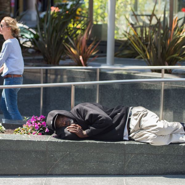 A woman pushes a stroller along while a homeless man sleeps in downtown San Francisco's Union Square in California on June, 28, 2016. (Credit: JOSH EDELSON/AFP/Getty Images)