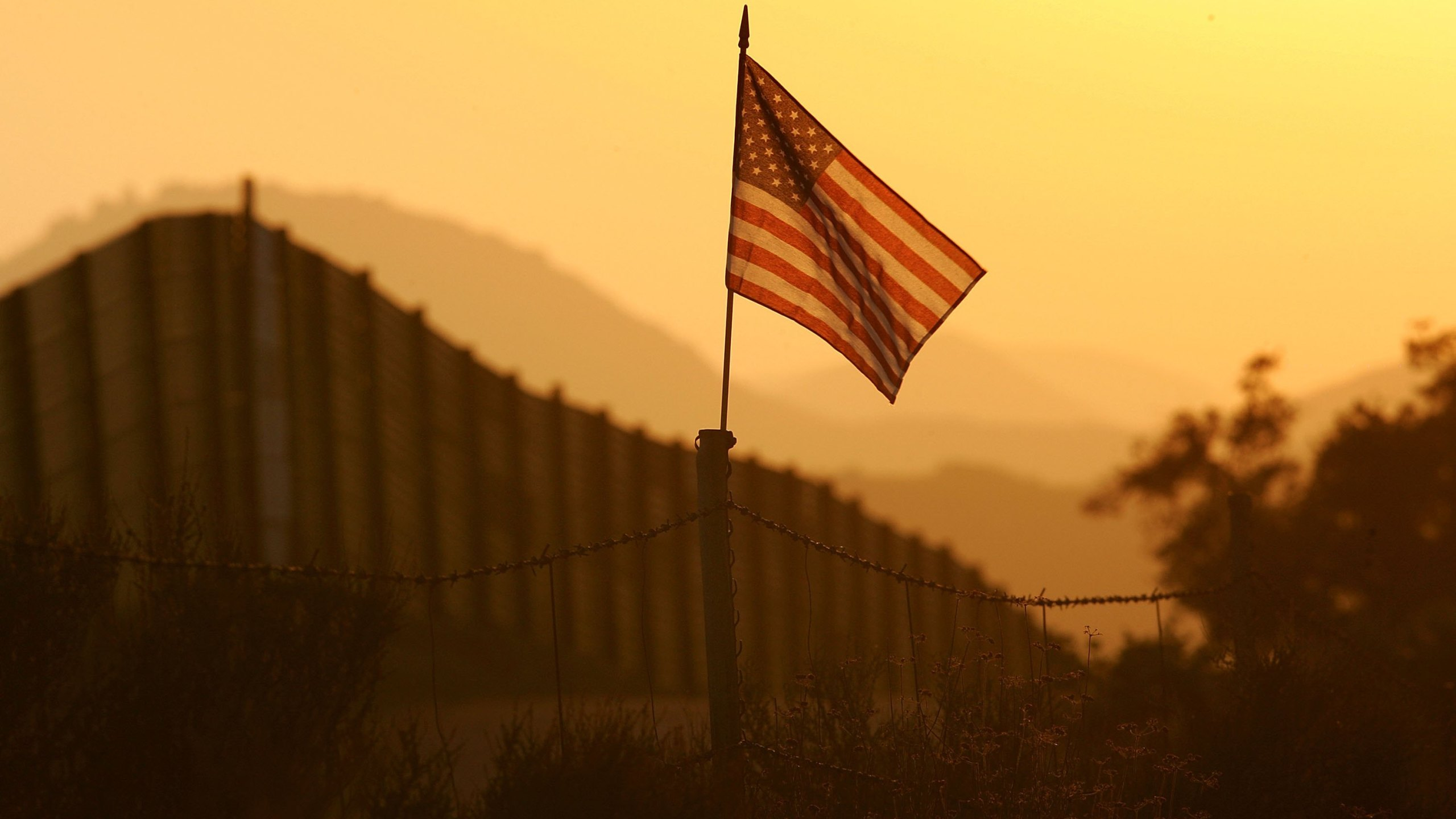An American flag flies near the US-Mexico border fence in an area where they search for border crossers October 8, 2006 near Campo, California. (Credit: David McNew/Getty Images)