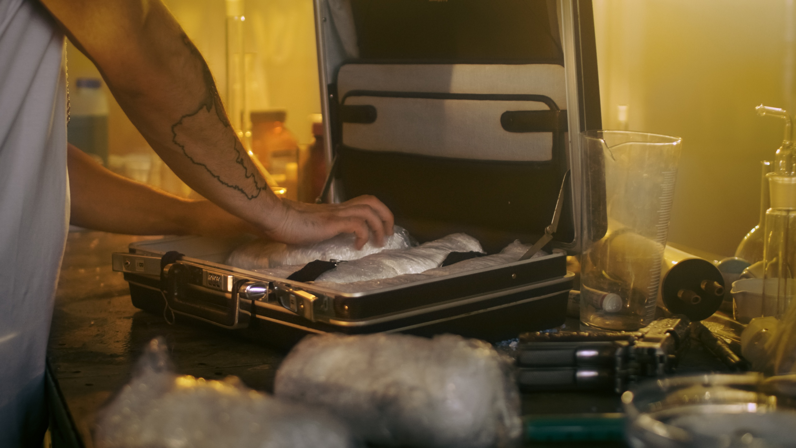 A man places brick packs filled with drugs into a suitcase. (Credit: iStock / Getty Images Plus)