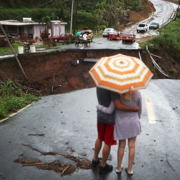 People look on at a section of a road that collapsed and continues to erode days after Hurricane Maria swept through the island on October 7, 2017 in Barranquitas, Puerto Rico. (Credit: Joe Raedle/Getty Images)
