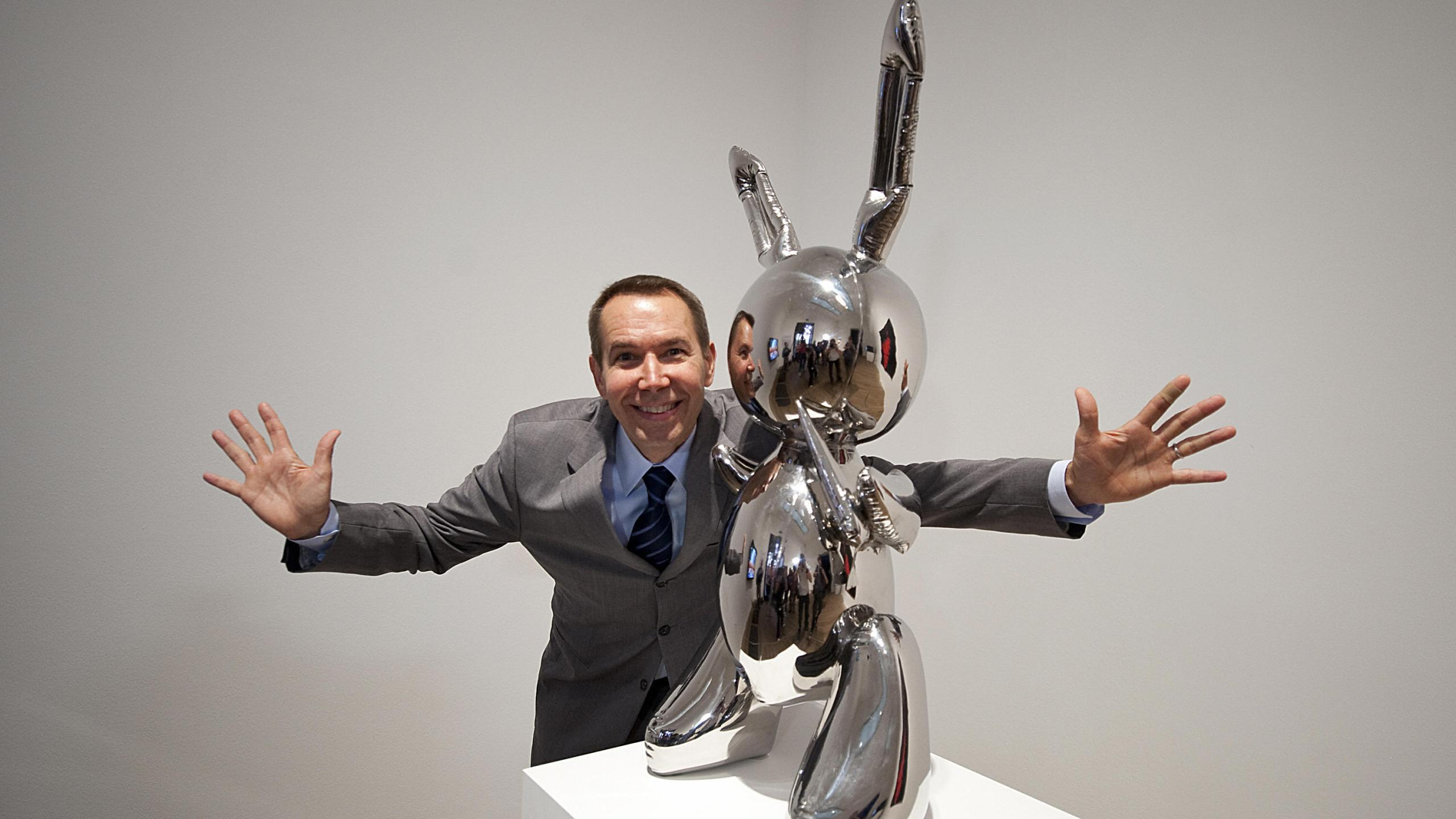 Artist Jeff Koons poses for photographs with his work of art entitled 'Rabbit 1986' during the press view of the 'Pop Life, Art In A Material World' exhibition at the Tate Modern, in London, on September 29, 2009. (Credit: BEN STANSALL/AFP/Getty Images)