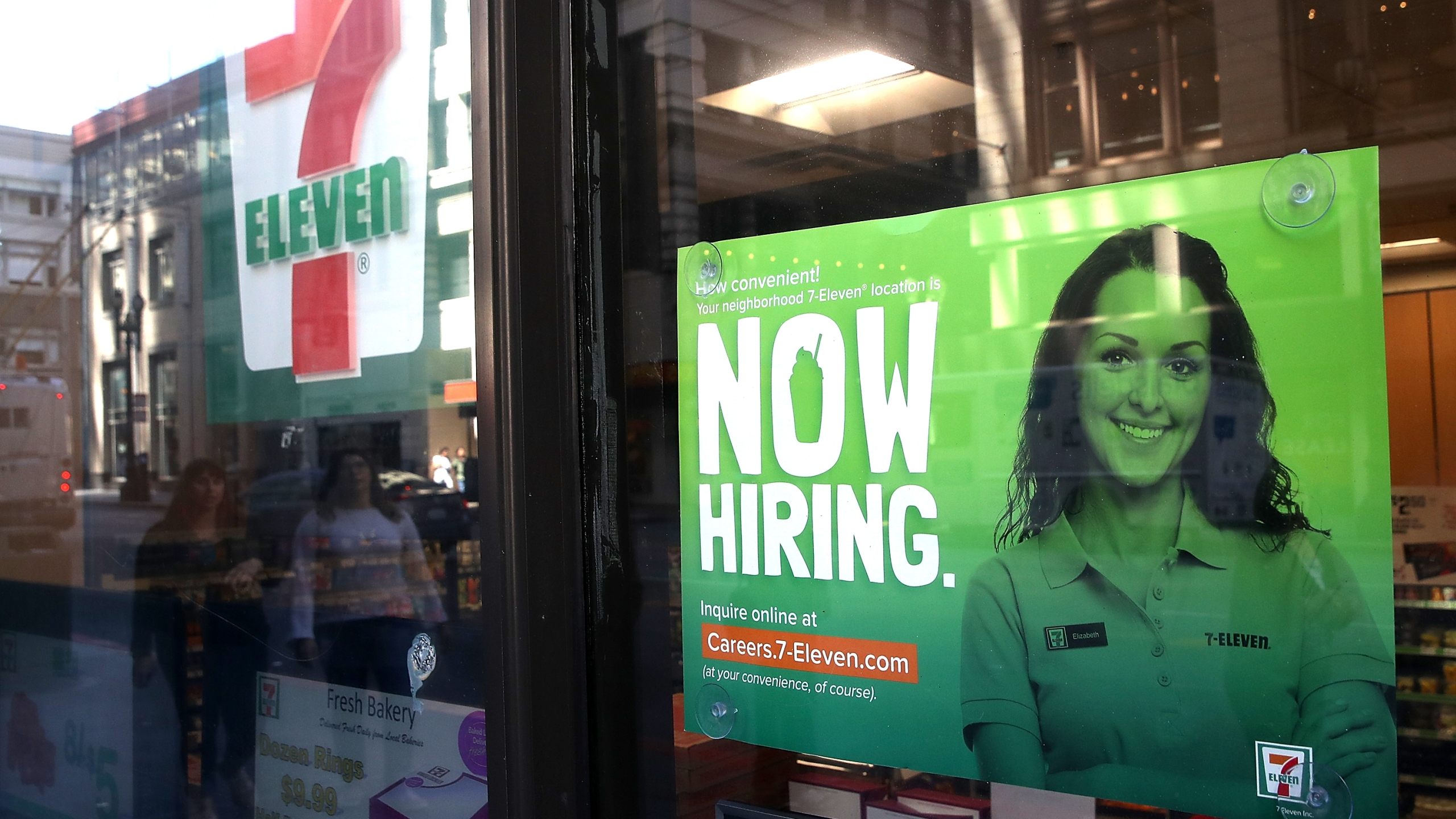A now hiring sign is posted on the window of a 7-Eleven store on June 1, 2018 in San Francisco. (Credit: Justin Sullivan/Getty Images)