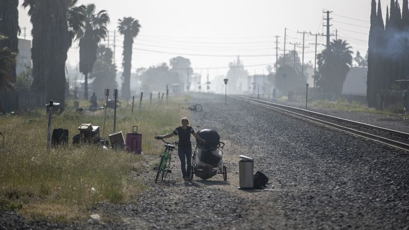 A homeless woman walks along the railroad right-of-way after Los Angeles police officers order homeless people out of an encampment in Chatsworth in April 2019. (Credit: Brian van der Brug / Los Angeles Times)