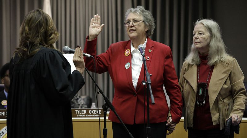 Jackie Goldberg, standing with wife Sharon Stricker, takes the oath of office Tuesday as an L.A. school board member from retired Judge Teresa Sanchez-Gordon. Goldberg had an immediate impact. (Credit: Myung J. Chun / Los Angeles Times)