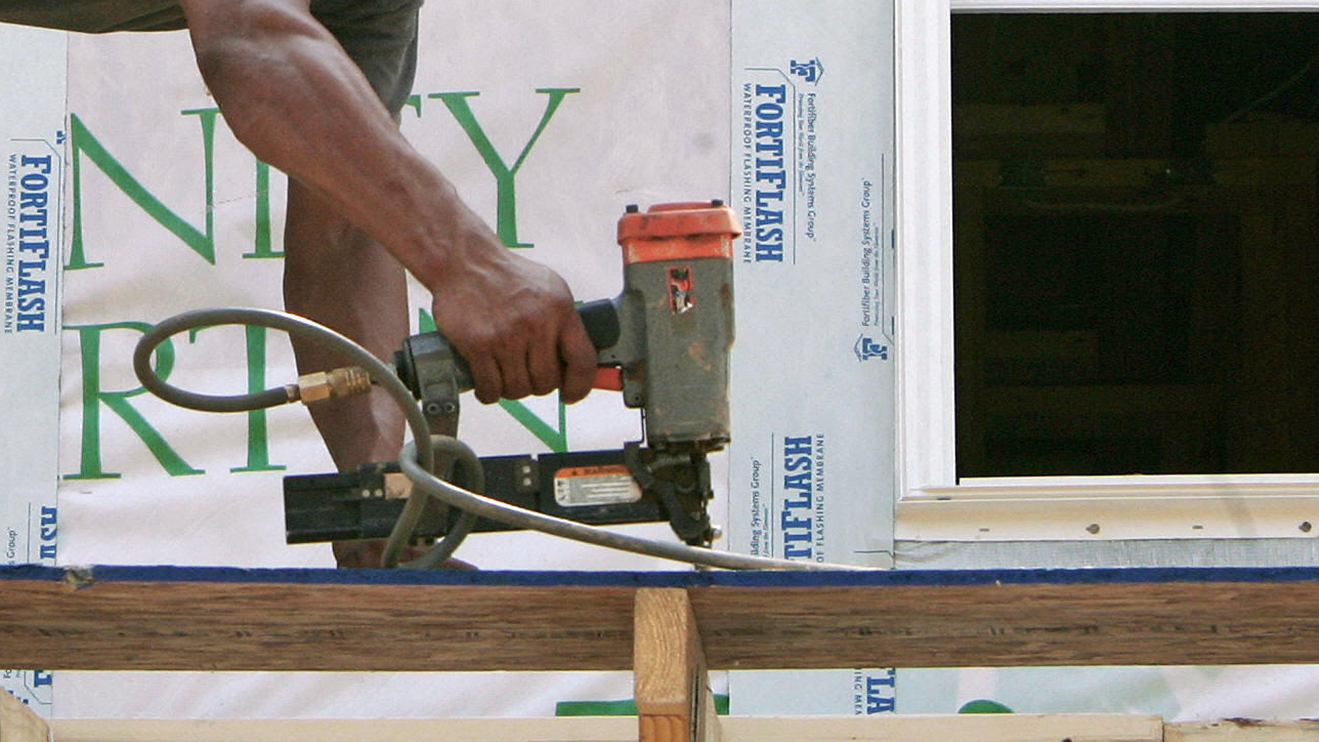 CENTREVILLE, UNITED STATES: (FILES) This 27 July, 2005 file photo shows a construction worker using his nail-gun during construction of a single family home in the Washington, DC, suburb of Centreville, Virginia. (Credit: Paul J. Richards/AFP/Getty Images)