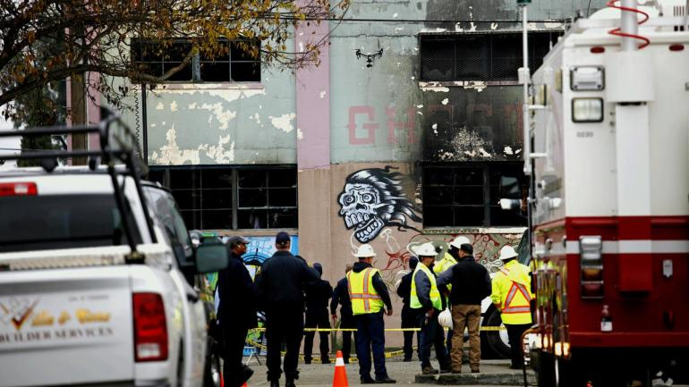 A drone flies over investigators outside the Oakland warehouse where at least 36 people died on Dec. 2, 2016. (Credit: Jay L. Clendenin/Los Angeles Times)