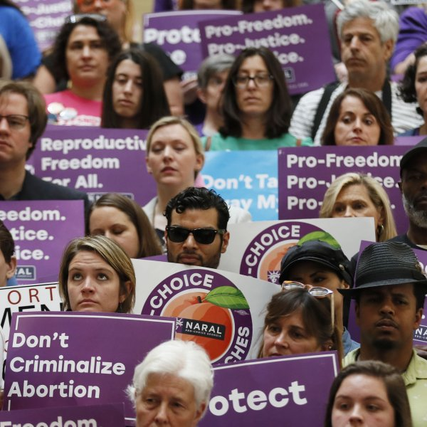 Abortion rights supporters stand during a news conference by Presidential candidate Sen. Kirsten Gillibrand, D-N.Y., at the Georgia State Capitol in Atlanta on Thursday, May 16, 2019 to discuss abortion bans in Georgia and across the country. (Credit: Atlanta Journal-Constitution/AP)