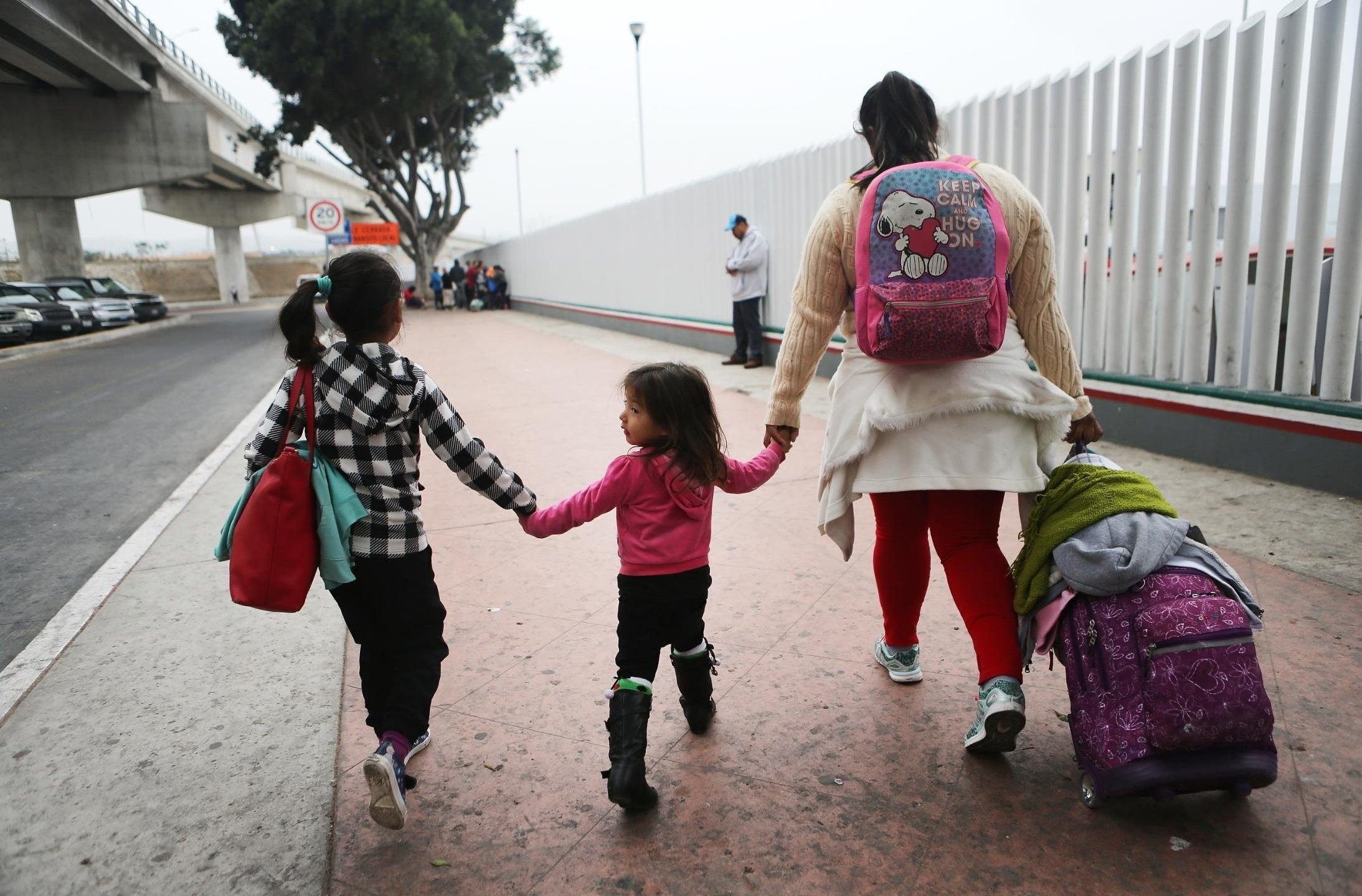 A migrant mother walks with her two daughters on their way to cross the port of entry into the U.S. in this June 2018 photo. A 10-year-old Salvadoran girl who died in Department of Health and Human Services custody last September was identified Friday by a US Customs and Border Protection official as Darlyn Cristabel Cordova-Valle. (Credit: CNN)