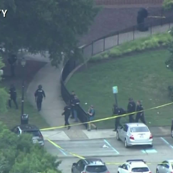 Officers are seen at the site of a shooting at a Virginia Beach municipal center that left at least 11 people dead on May 31, 2019. (Credit: WAVY)
