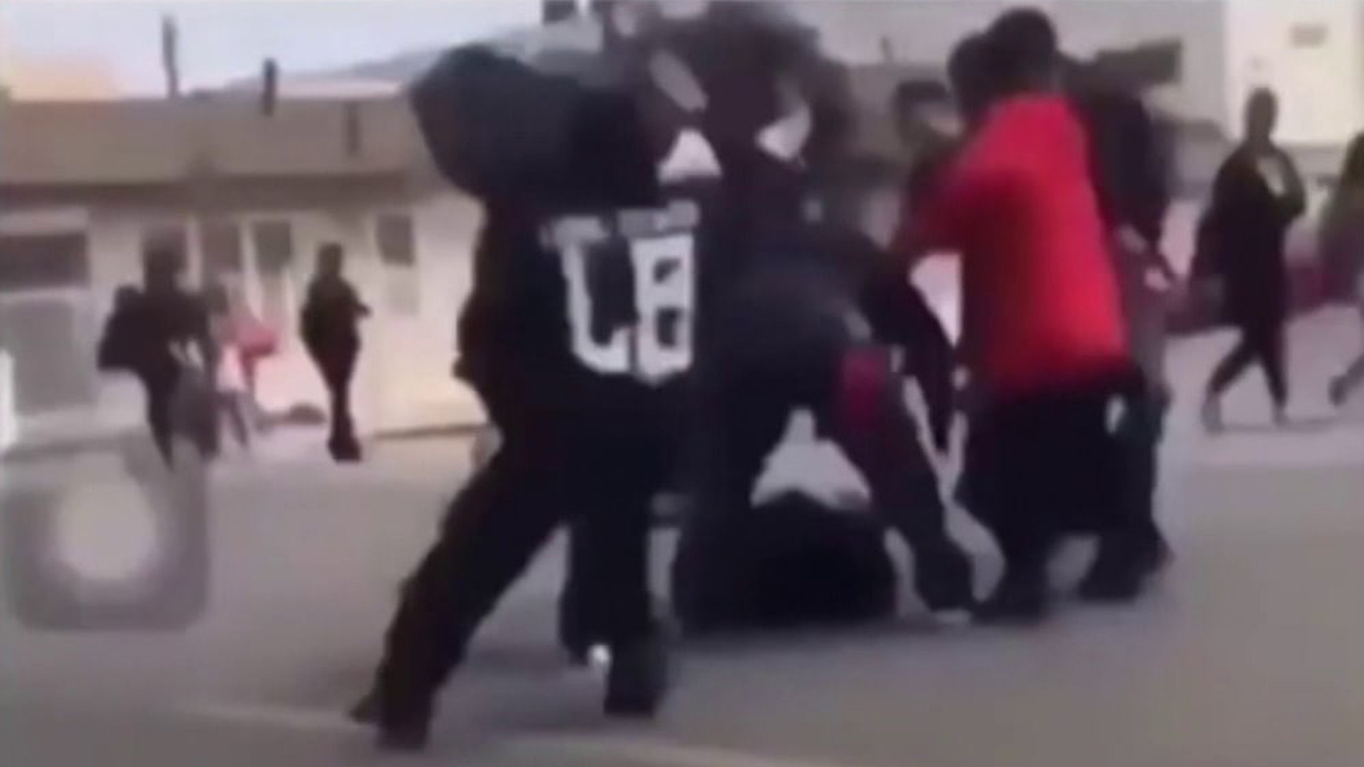A still from cellphone video shows a student being attacked by others outside a high school in Long Beach.