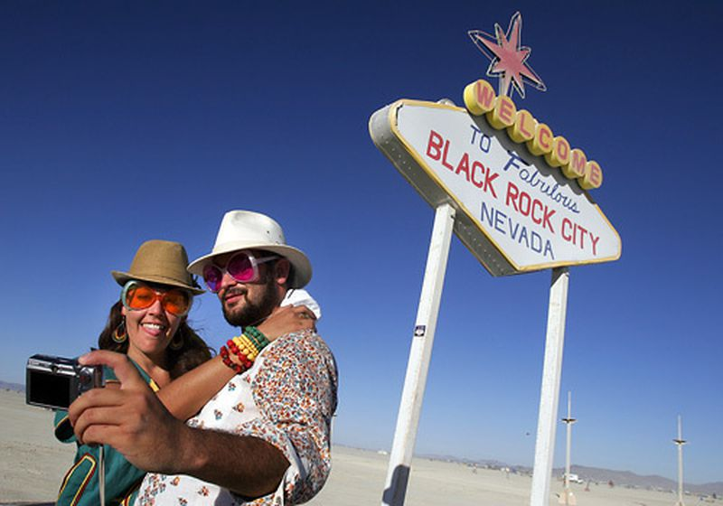 Simone Oliver of San Diego and Eric Weisz of San Francisco take a picture in front of a welcome to Black Rock City sign at Burning Man 2008. (Credit: Spencer Weiner / Los Angeles Times)