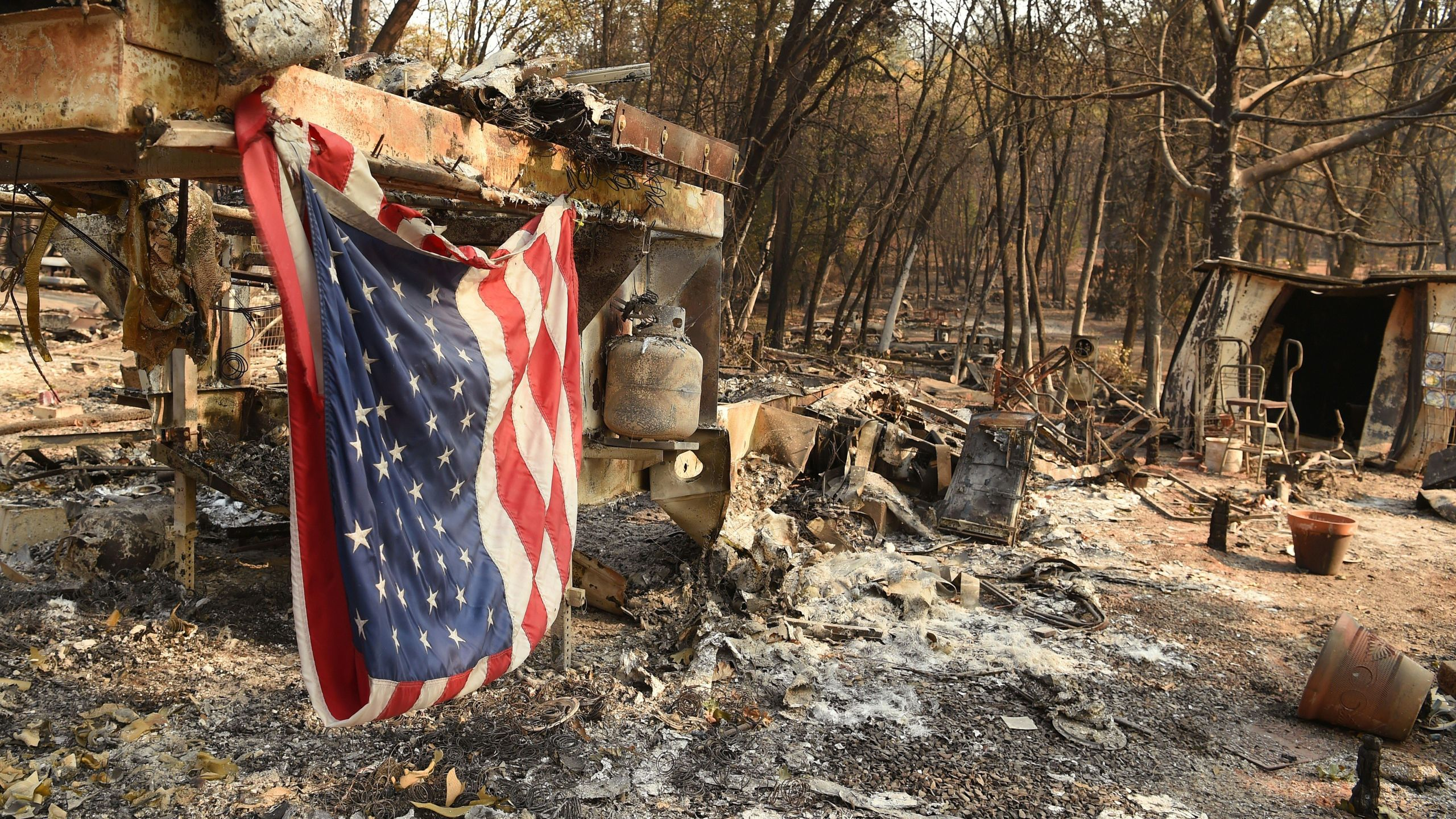 An American flag hangs at a burned out mobile home park in Paradise, California on Nov. 18, 2018. (JOSH EDELSON/AFP/Getty Images)