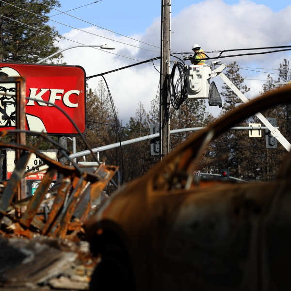 A worker repairs a utility line next a KFC restaurant in Paradise that was destroyed by the Camp Fire, Feb. 11, 2019. (Credit: Justin Sullivan / Getty Images)