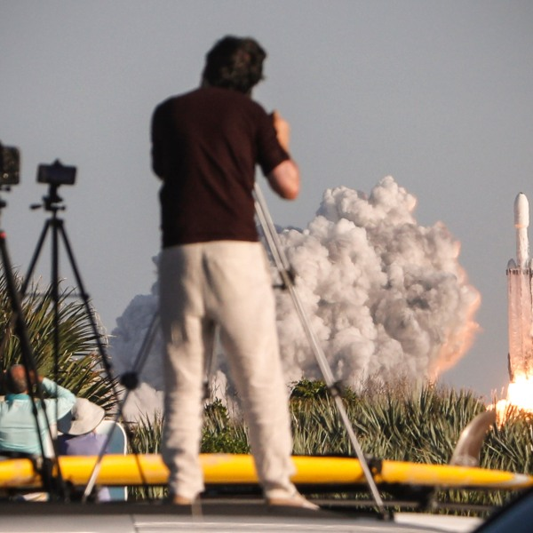 Visitors at Playalinda Beach look on as a SpaceX Falcon Heavy rocket launches from Pad 39B at the Kennedy Space Center in Florida, on April 11, 2019. (Credit: GREGG NEWTON/AFP/Getty Images)