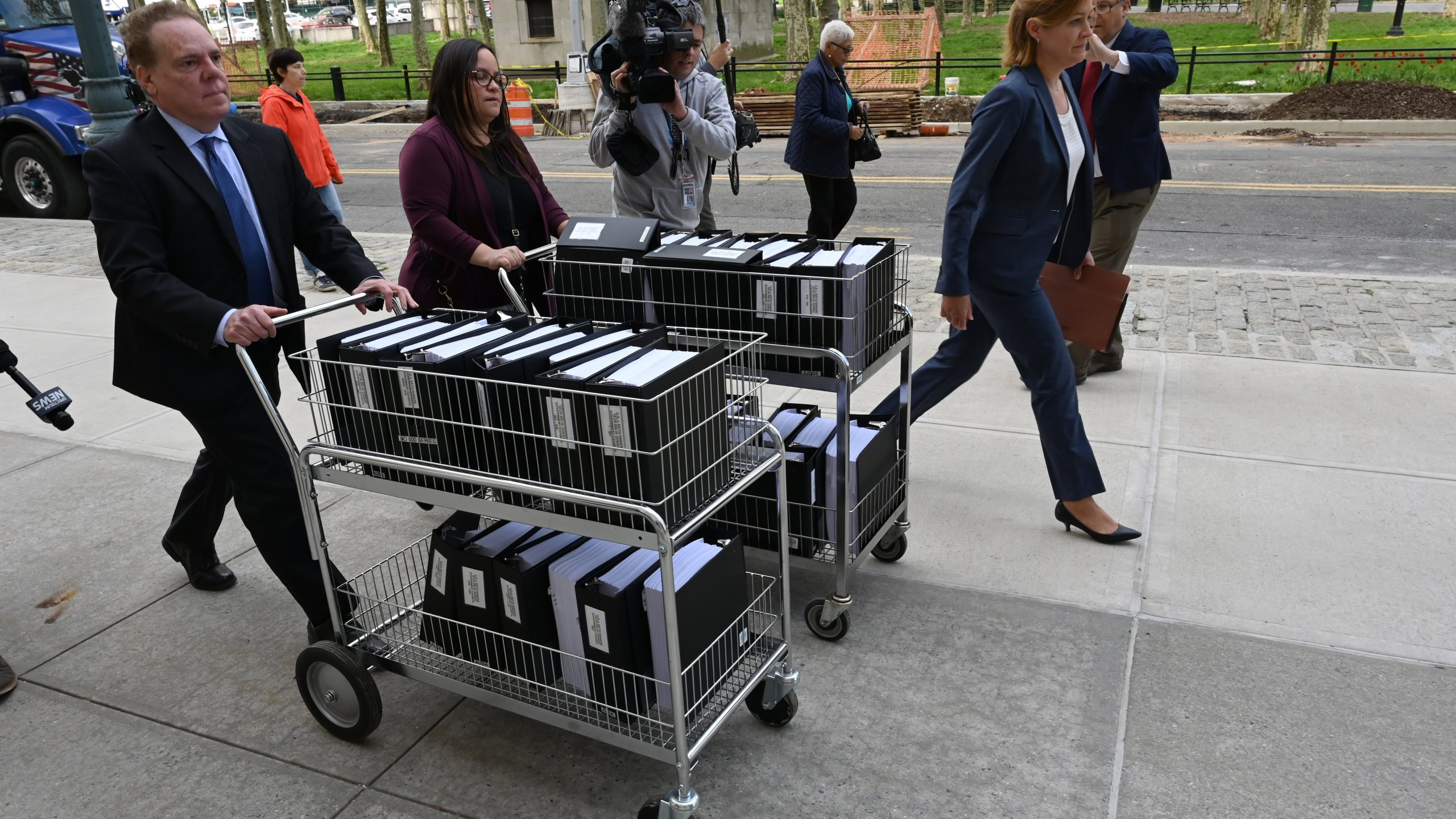 Members of the prosecution in the Nxivm case arrive with documents at Brooklyn Federal Court on May 7, 2019, for day one of the trial of Keith Raniere, founder of Nxivm. (Credit: TIMOTHY A. CLARY/AFP/Getty Images)