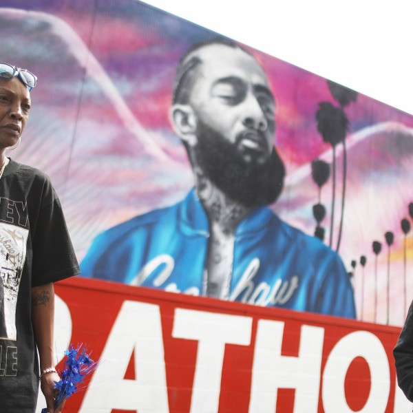 Fans gather in front of a mural to slain rapper Nipsey Hussle as they await outside The Marathon Clothing store for his funeral procession in South Los Angeles on April 11, 2019. (Credit: Mario Tama / Getty Images)