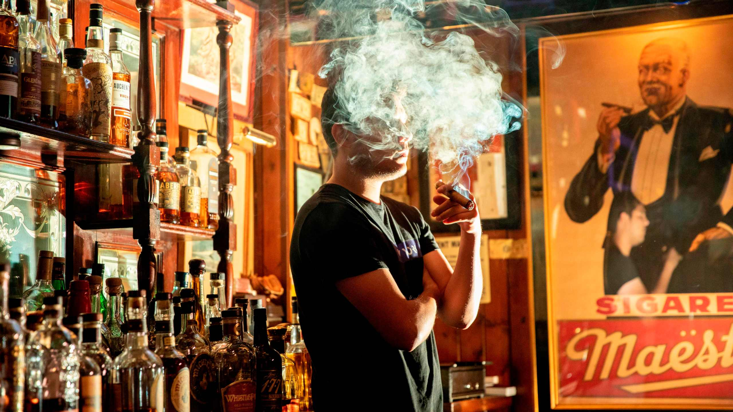 Marc Dominguez, bartender at Buena Vista Cigar Club, smokes a cigar in the Beverly Hills lounge on May 21, 2019. (Credit: Kyle Grillot / AFP / Getty Images)