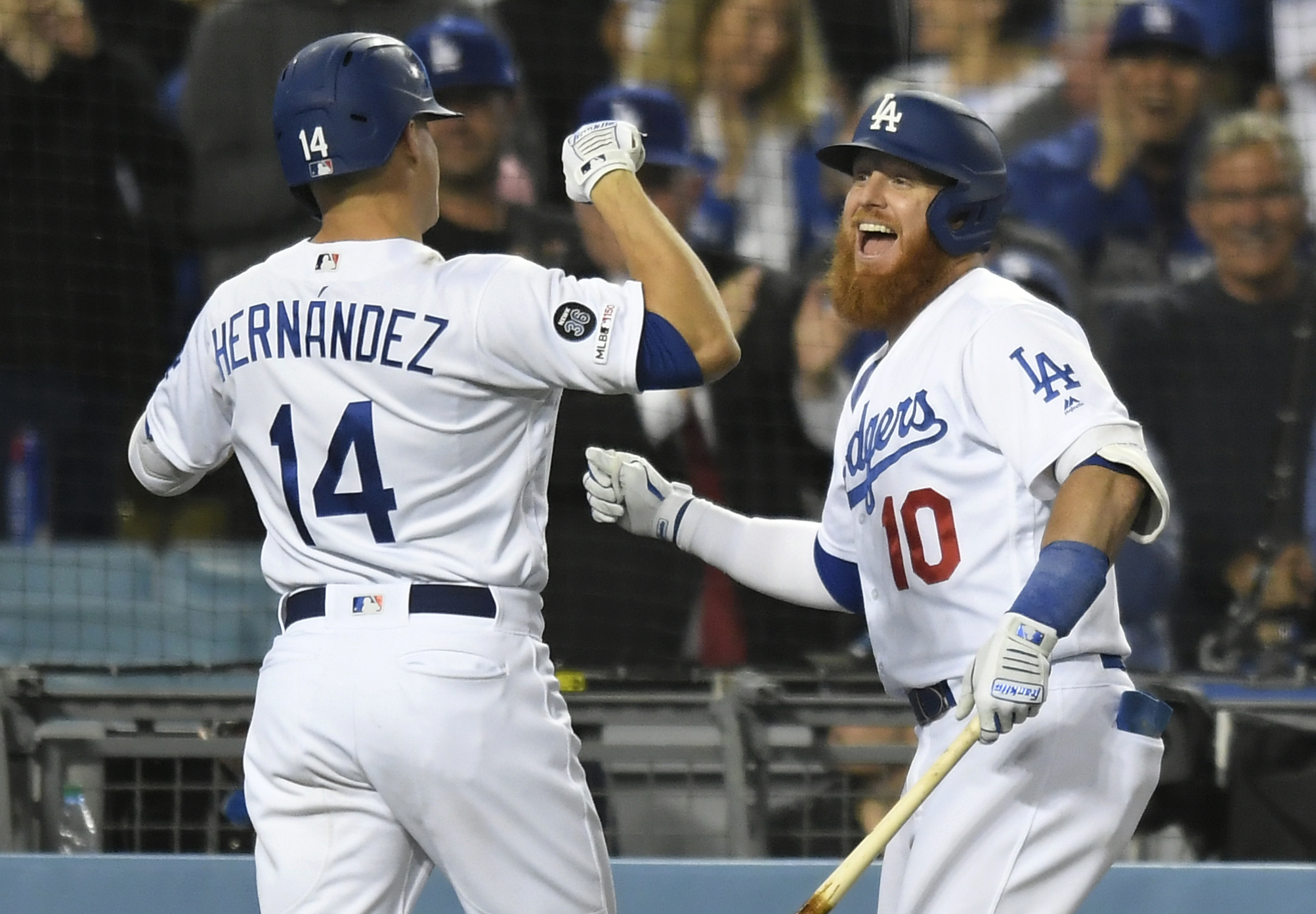 Justin Turner congratulates Enrique Hernandez of the Los Angeles Dodgers on his grand slam home run against the San Francisco Giants in the seventh inning at Dodger Stadium on June 18, 2019. (Credit: John McCoy/Getty Images)