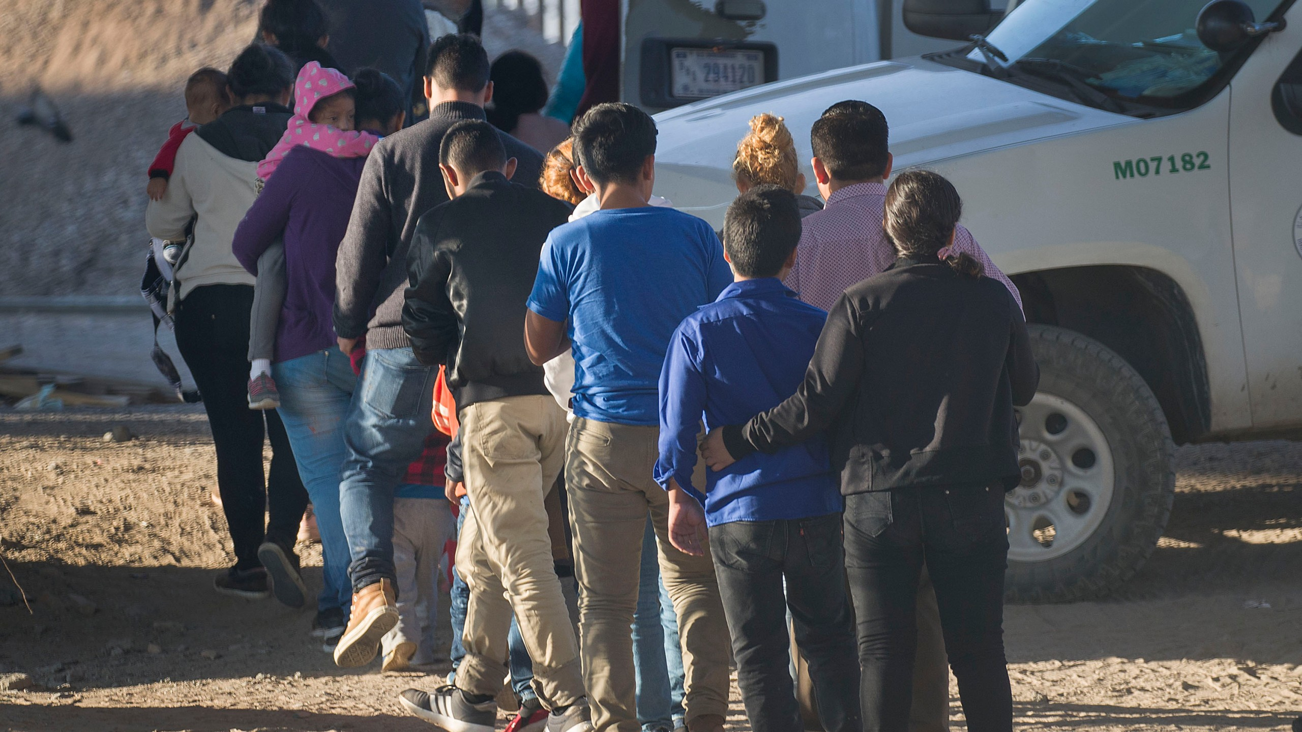 Migrants wait to be processed and loaded onto a bus by U.S. border agents after being detained when they crossed illegally into El Paso, Texas, from Mexico on June 2, 2019. (Credit: Joe Raedle / Getty Images)