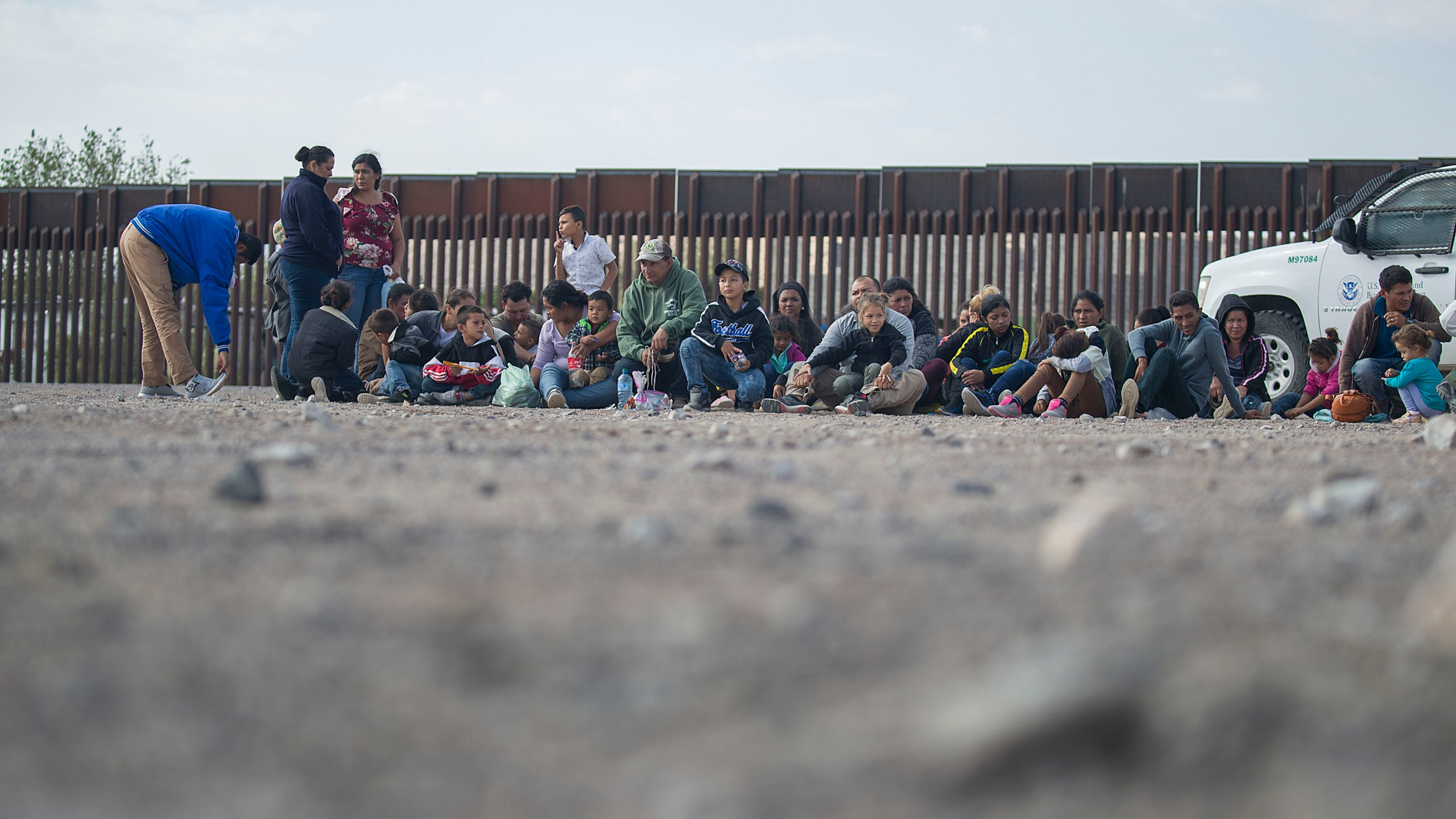 Migrants wait to be processed and loaded onto a bus by Border Patrol agents after being detained when they crossed illegally into the United States from Mexico on June 02, 2019 in Sunland Park, New Mexico. (Credit: Joe Raedle/Getty Images)