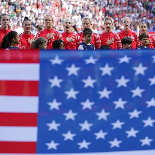 U.S. players sing the national anthem behind the flag before facing Chile in the 2019 FIFA Women's World Cup France group F match at Parc des Princes on June 16, 2019 in Paris, France. (Credit: Richard Heathcote/Getty Images)