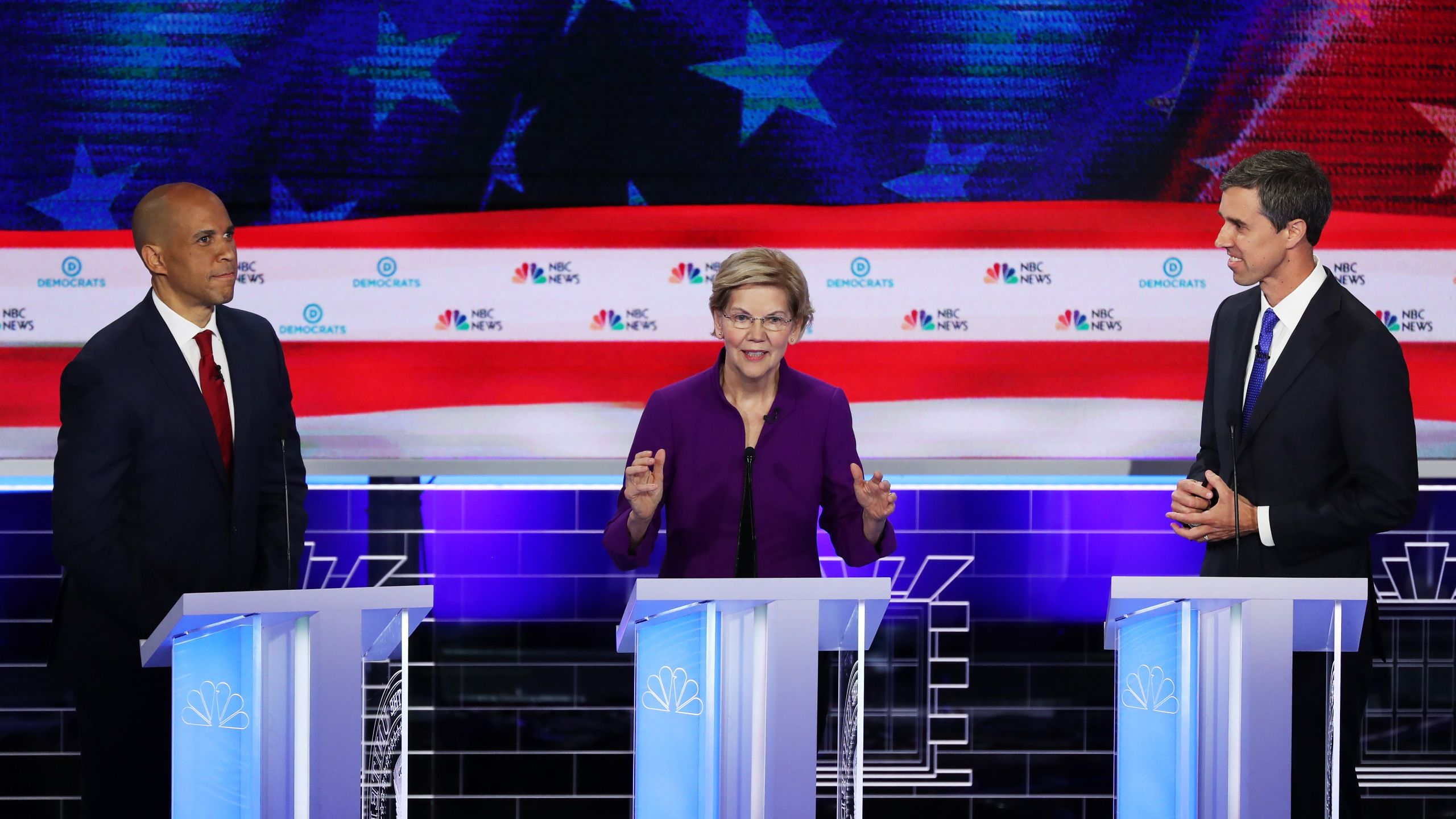 Sen. Elizabeth Warren (D-MA) speaks as Sen. Cory Booker (L) (D-NJ) and former Texas congressman Beto O'Rourke look on during the first night of the Democratic presidential debate on June 26, 2019 in Miami, Florida. (Credit: Joe Raedle/Getty Images)