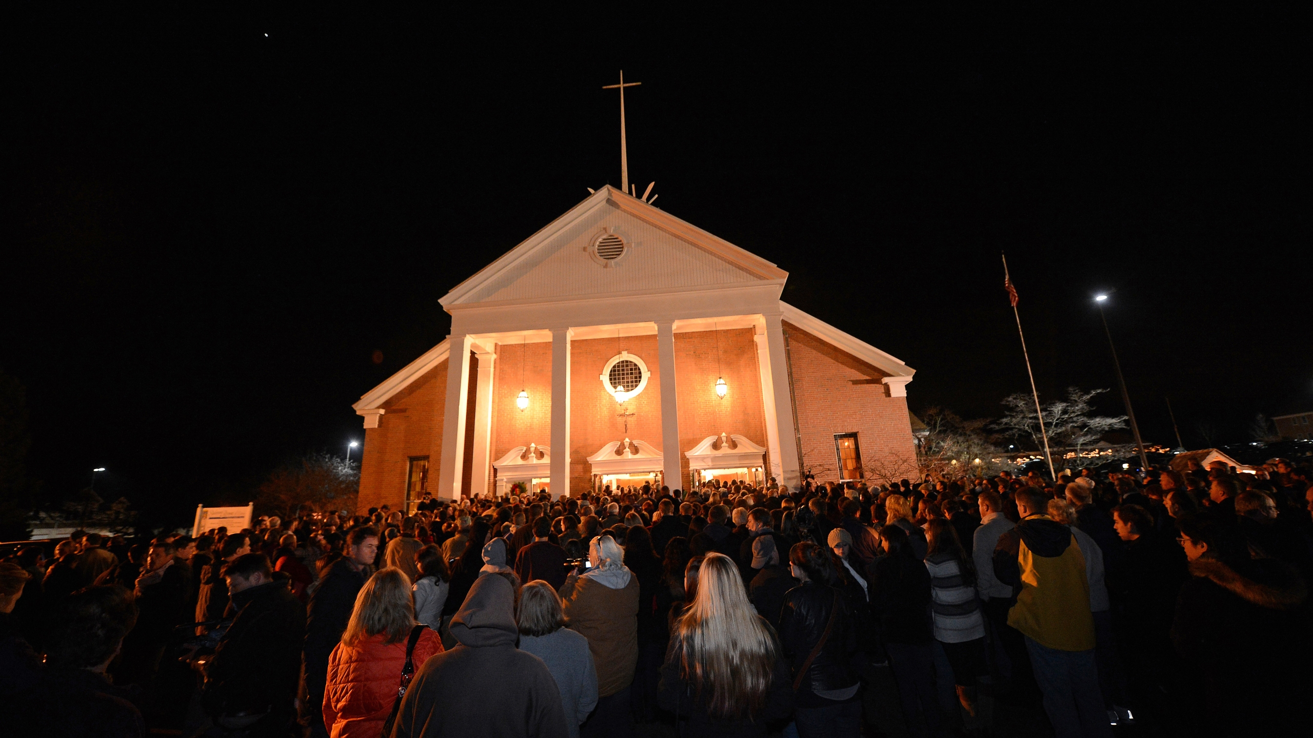 People gather for a prayer vigil at St. Rose Church following the shooting at Sandy Hook Elementary School that killed 26 people, including 20 children, in Newtown, Conn., Dec. 14, 2012. (Credit: EMMANUEL DUNAND/AFP/Getty Images)