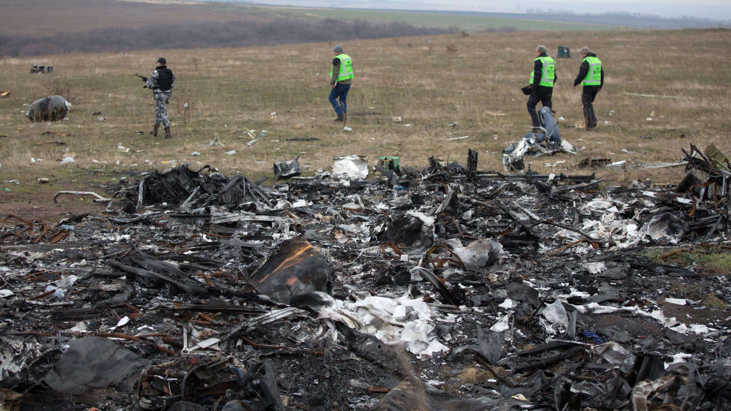 Dutch investigators accompanied by pro-Russian armed rebels arrive near parts of the Malaysia Airlines Flight MH17 at the crash site near the Grabove village in eastern Ukraine on Nov. 11, 2014. (Credit: MENAHEM KAHANA/AFP/Getty Images)