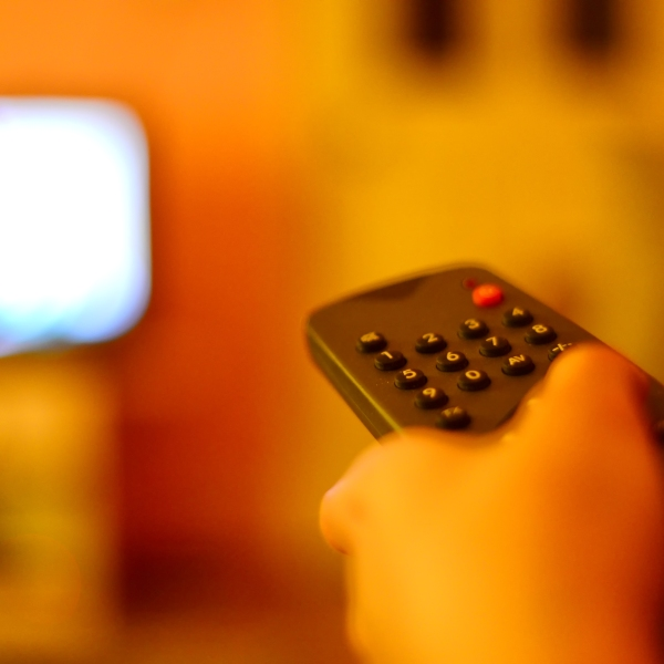 A file image shows a person with a TV remote. (Credit: iStock / Getty Images Plus)