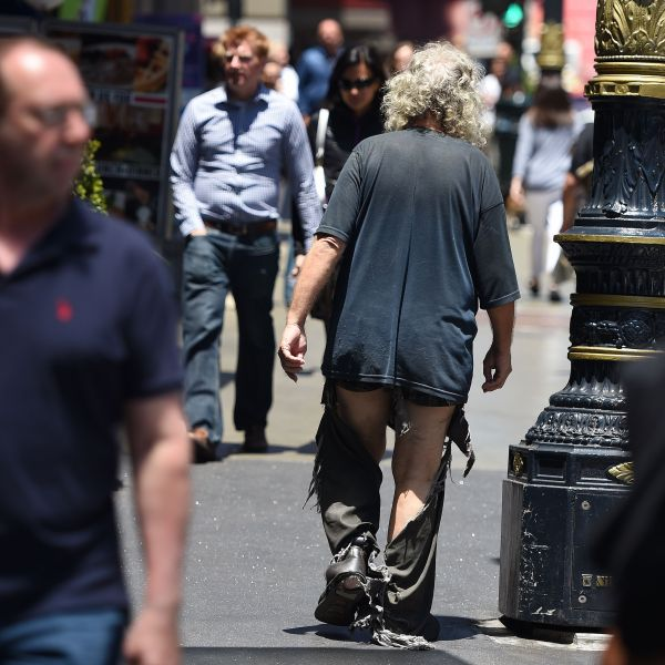 A homeless man walks in tattered clothing along a sidewalk in downtown San Francisco on June, 28, 2016. (Credit: Josh Edelson / AFP / Getty Images)