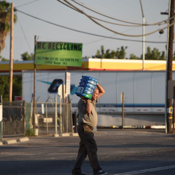 A man carries a case of water from a store to his car on Aug. 24, 2016, in Porterville, a Central Valley farming community where many families do not have a hookup for city water and depend on well water, which tests show contains dangerously high levels of nitrates. (Credit: Robyn Beck / AFP / Getty Images)