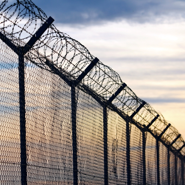 Barb wire is seen outside a prison in this file photo. (Credit: iStock / Getty Images Plus)