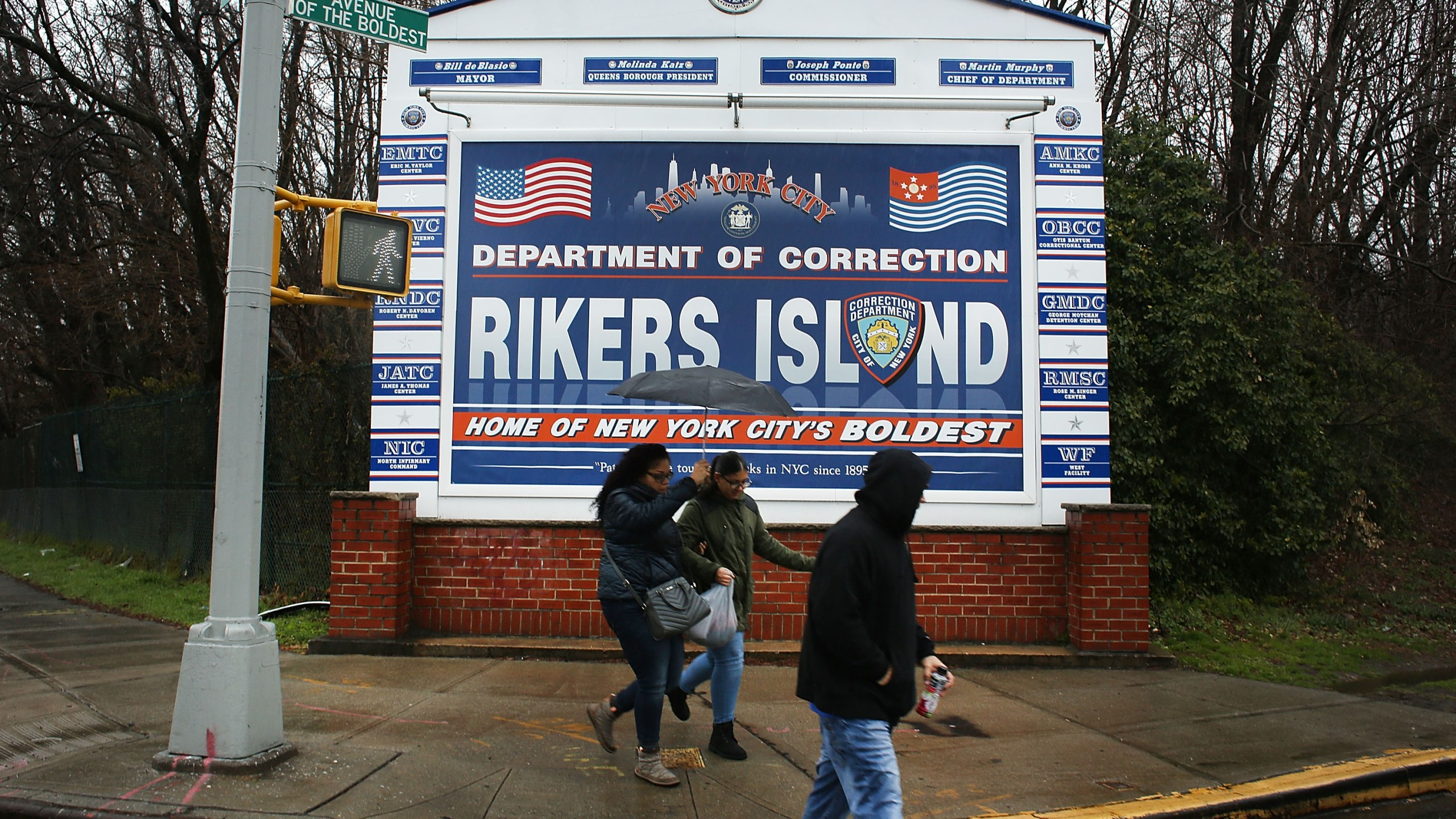 People walk by a sign at the entrance to Rikers Island on March 31, 2017 in New York City. (Credit: Spencer Platt/Getty Images)