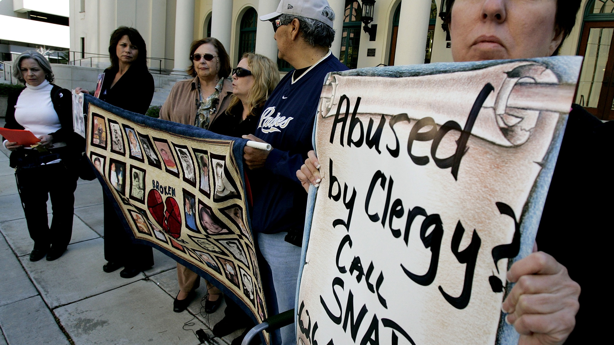 Protestors and alleged sexual abuse victims stand outside of The Jacob Weinburg Couthouse during a vigil to bring attention to victims of sexual abuse by religious leaders within the Catholic church on March 1, 2007 in San Diego, California. (Credit: Sandy Huffaker/Getty Images)