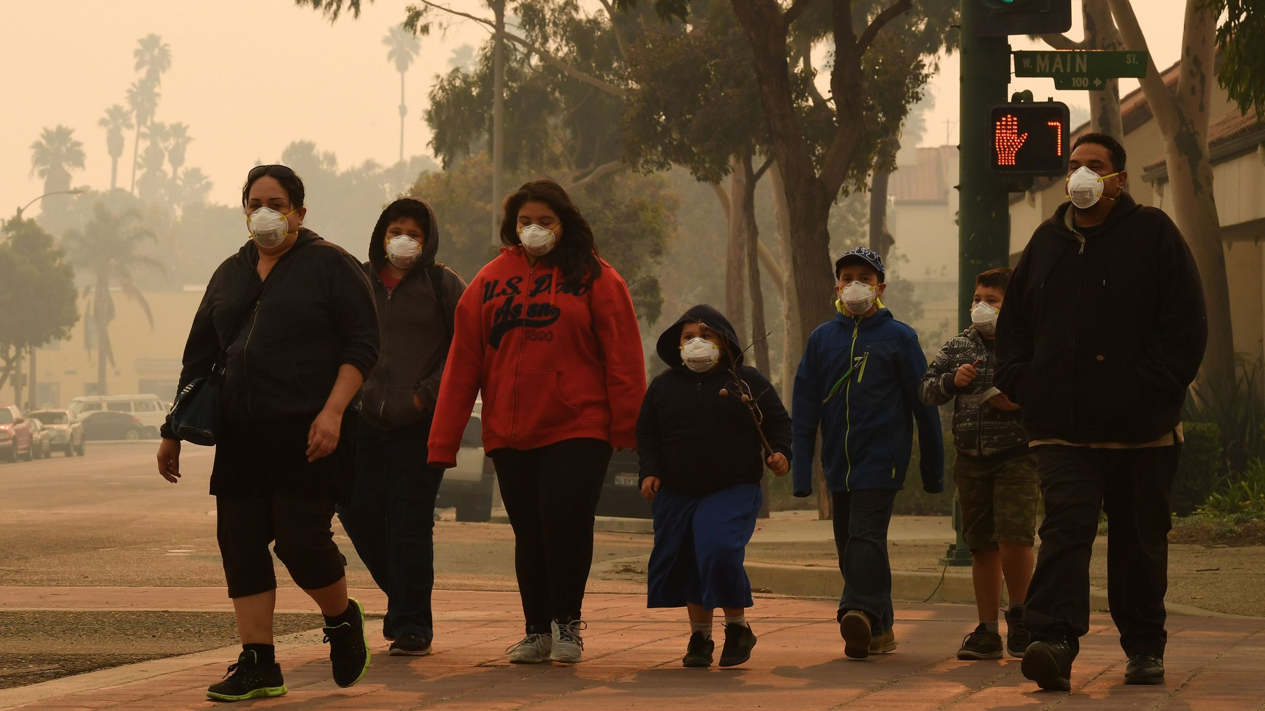 A family wears face masks as they walk through the smoke filled streets after the Thomas Fire swept through Ventura on Dec. 6, 2017.