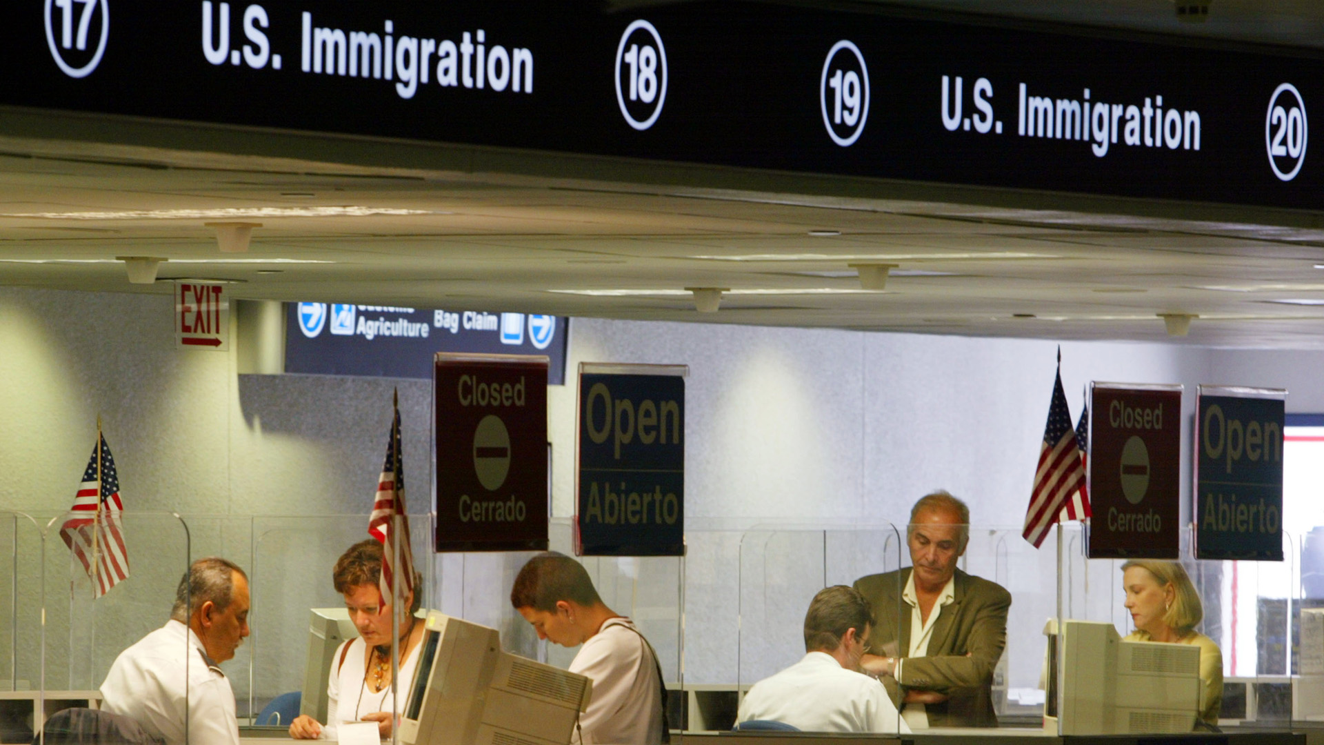 U.S. Immigration inspectors check passports July 2, 2002 at Miami International Airport in Miami, Forida. (Credit: Joe Raedle/Getty Images)