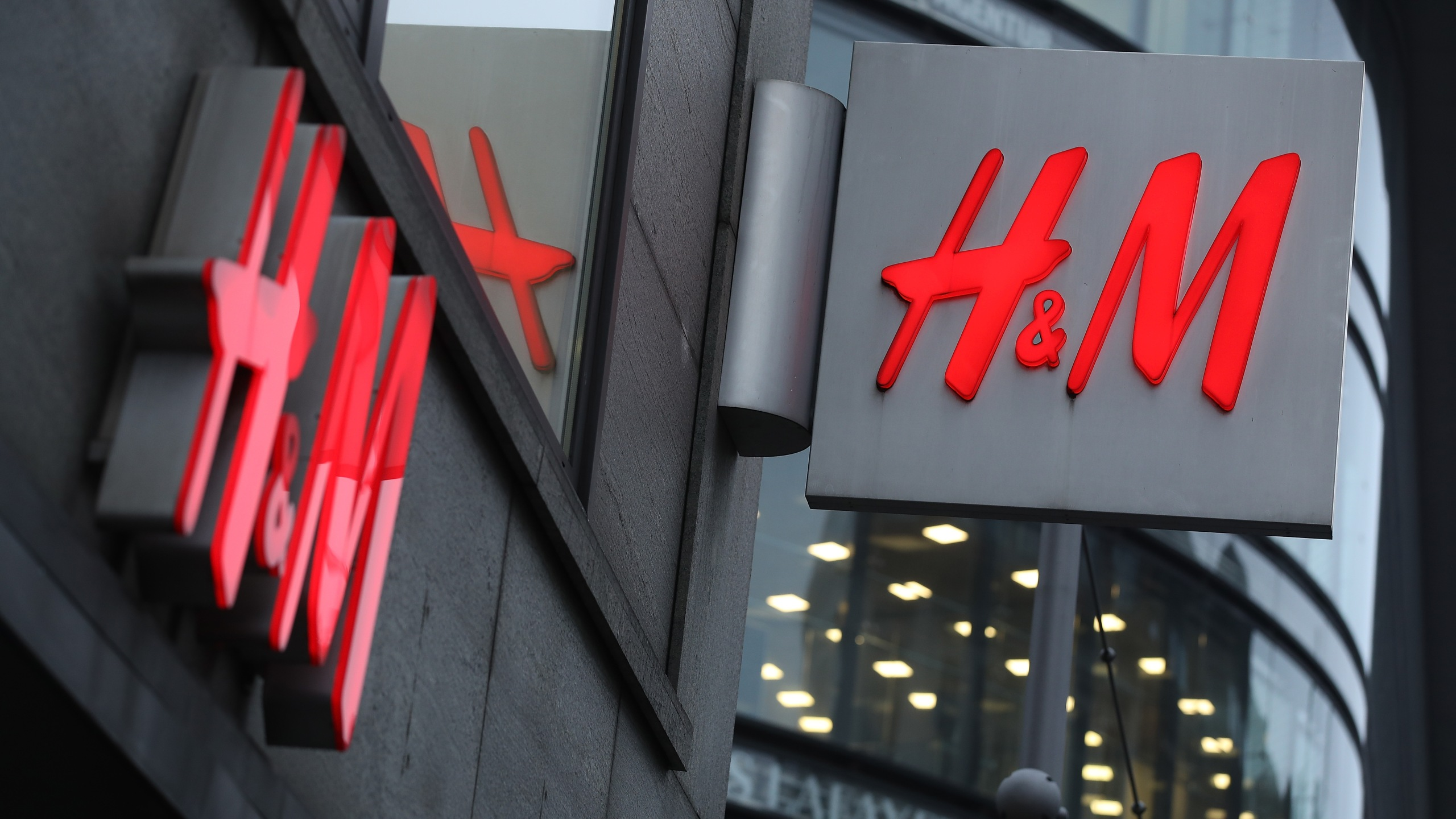 The logo of Swedish clothing retailer H&M hangs over one of its stores on March 28, 2018 in Berlin, Germany. (Credit: Sean Gallup/Getty Images)
