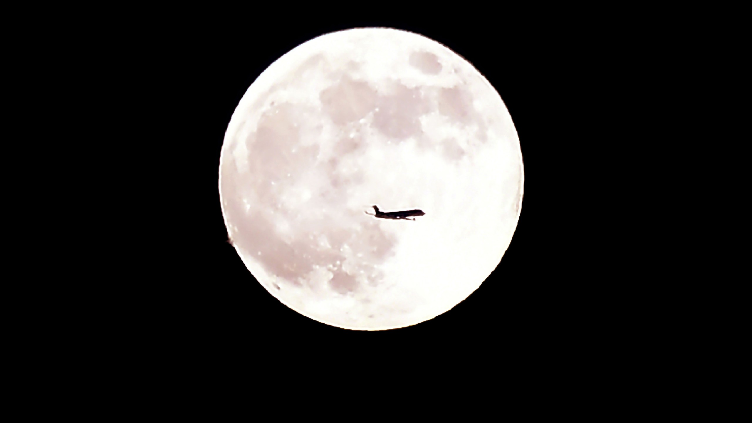 An airplane flies past June's full moon known as the Strawberry Moon on June 27, 2018 in Montebello, California. (Credit: FREDERIC J. BROWN/AFP/Getty Images)