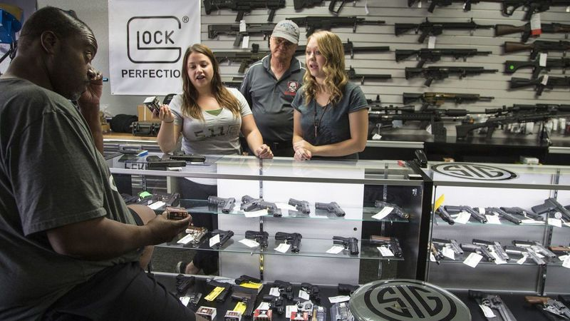 Store managers Jamie Taflinger, left, and Kendyll Murray show customer Cornell Hall different types of ammo at the Get Loaded gun store in Grand Terrace. (Credit: Gina Ferazzi / Los Angeles Times)