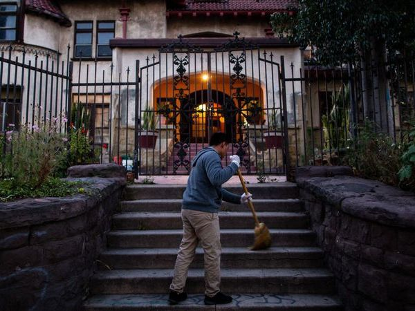 Resident Hildner Coronado Atjun sweeps the front stairs of Casa Libre in May 2019. (Credit: Kent Nishimura / Los Angeles Times)