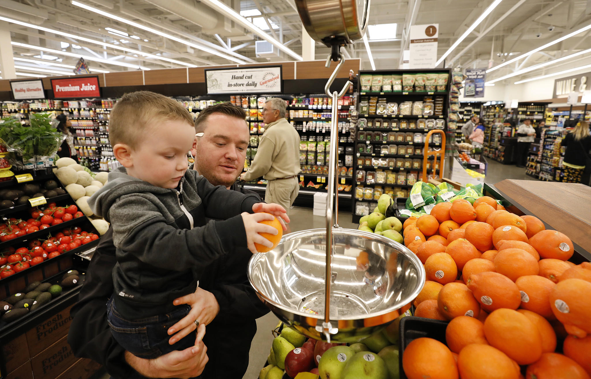 Zachary Reitz, who has vacationed on Catalina Island since he was a child, holds his 3-year-old son Jace Reitz as he weighs fruit at the new Vons Avalon Market on Catalina Island. (Credit: Al Seib / Los Angeles Times)