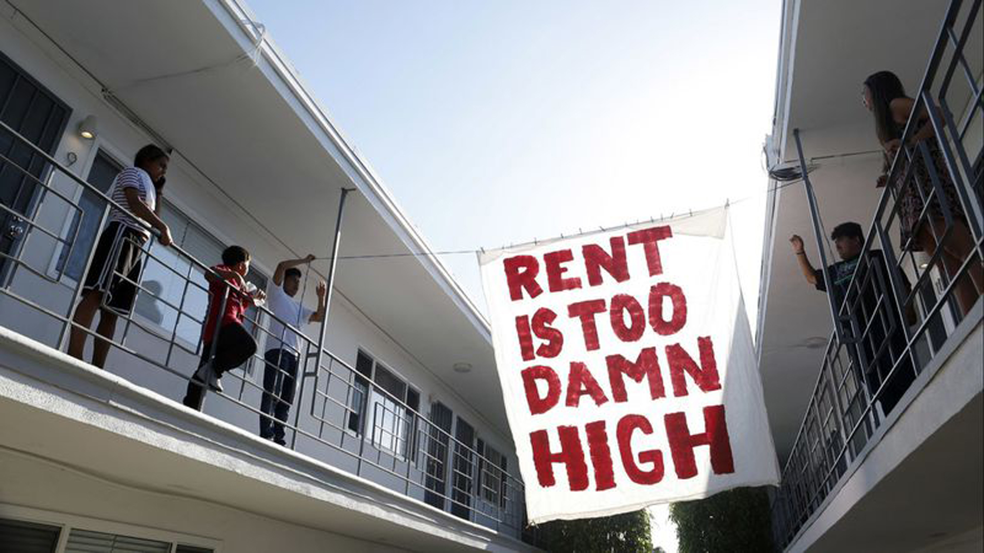 Organizers with Housing Long Beach, a local advocacy group, hang up a sign in the courtyard of an apartment complex on Cedar Avenue in Long Beach. (Credit: Katie Falkenberg / Los Angeles Times)