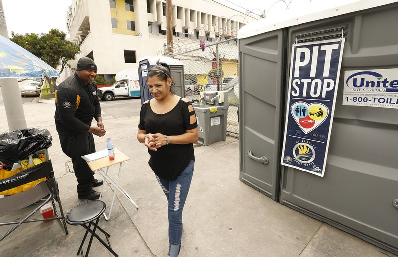 Brenda Chavando thanks Deandre Fradiue who works as the attendant at the portable Pit Stop toilets at Oakwood and Madison Avenues in East Hollywood in June 2019. (Credit: Al Seib / Los Angeles Times)
