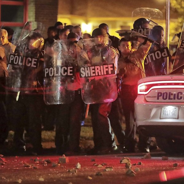 Shelby County Sheriff's deputies brace against the crowd as protesters throw rocks. (Credit: Jim Weber/AP via CNN Wire)