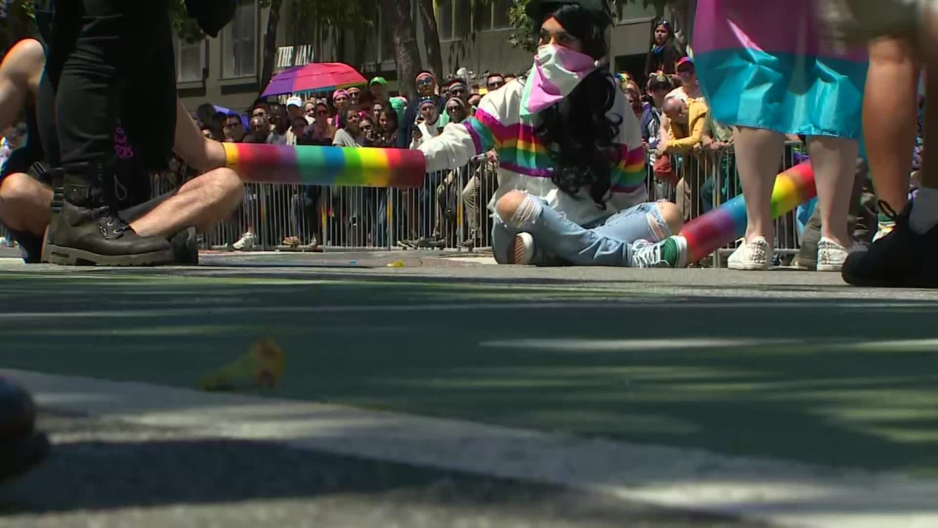 Protesters link arms while dressed in rainbow colors as they block a street during Pride festivities in San Francisco on June 30, 2019. (Credit: CNN)