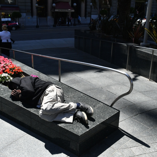 A homeless man sleeps on a planter in San Francisco, California on Tuesday, June, 28, 2016. (Credit: ;JOSH EDELSON/AFP/Getty Images)