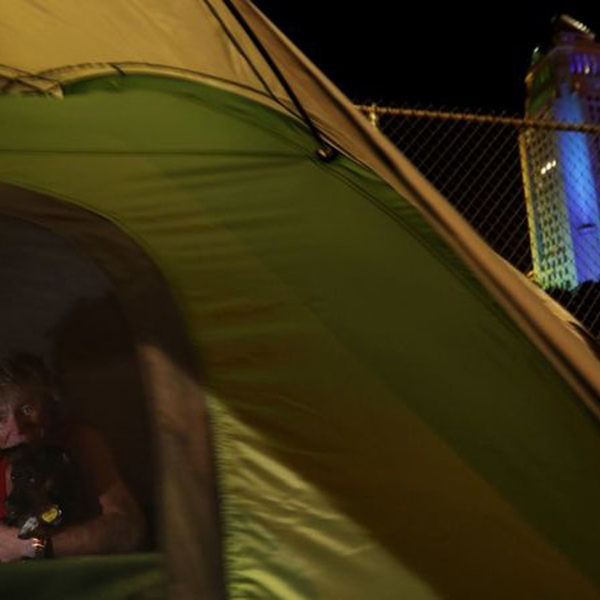 "Tamela Kerneghan, 52, sets up her tent near Los Angeles City Hall. A pest control company warned that the homeless created ""harborage for rodents."" (Credit: Luis Sinco / Los Angeles Times)"