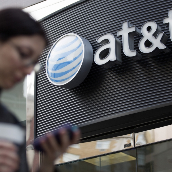 A woman checks her cellphone while walking past an AT&T store in this undated file photo. (Credit: Andrew Harper/Bloomberg/Getty Images)
